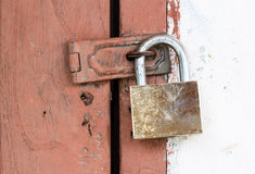 Door locked by brass padlock Stock Photo