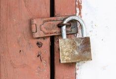 Door locked by brass padlock Stock Photo
