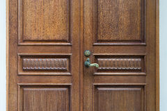 The door is made of carved wood with a vintage a handle Stock Photo