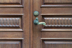 The door is made of carved wood with a vintage a handle Royalty Free Stock Image
