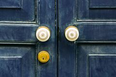 The door made of hardwood with ornate knobs and keyhole. The old vintage retro door made of hardwood with ornate knobs and keyhole. frontal view conceptual of Royalty Free Stock Photos