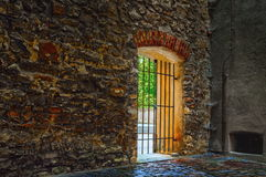 Door with metal grating in ancient wall made or irregular stones Stock Photography