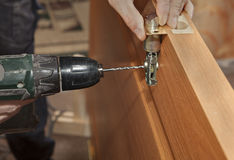 Door mounting, install deadbolt lock, electric drill drilled hol Stock Photos