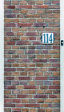 The door number. On the brick wall texture Stock Photos