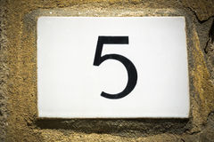 Door number five sign on weathered wall Stock Photos