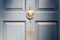 Door number one hundred and fifteen and knocker vignette look Stock Image