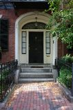 Door Number Thirty Seven Boston. Black door in Boston on a stately brownstone in the beacon hill area. With a brick walkway and wrought iron fence and a fox head Royalty Free Stock Images