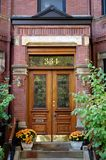 Door Number Three Hundred And Thirty Four Boston. Wooden double doorway in Boston with trees and flowers Stock Images