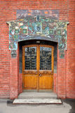 Door in the old brick house decorated with tiles Stock Images