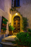Door in an old house decorated with flower at night Royalty Free Stock Photo