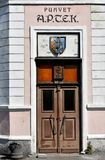 Door of an old pharmacy in parnu, Estonia. Entrance of an old pharmacy in Parnu, Estonia. over the door is an old wooden coat of arms of Parnu stock photo