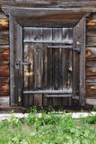 Door in an old village house with a padlock. Old wooden door in a village house with a padlock Royalty Free Stock Images