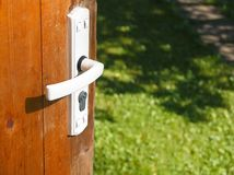 Door open in summer. Closeup of a door open and a summer garden in the blurred background royalty free stock image