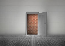 Door open to reveal red brick wall blocking the way. In a dull grey room Royalty Free Stock Image