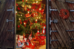 Door opening into a room with christmas tree and gift Stock Images
