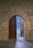Door opening to a beautiful cloudy sky. Door with arch opening to a beautiful cloudy sky royalty free stock photography