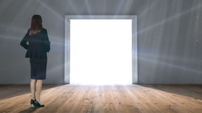Door opening to light watched by businesswoman