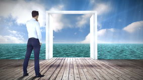 Door opening to ocean watched by businessman