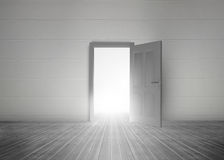 Door opening to reveal bright light. In a dull grey room Stock Photos