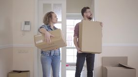 The door opens, tall man and pretty woman in casual dress with boxes in hands enters half empty room. Young people put stock video