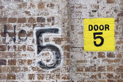No: Door 5 on brick wall Stock Photo