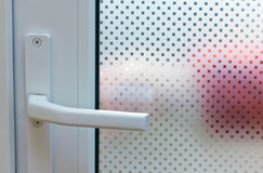 Door with patterned glass. Through patterned glass can be seen as someone opens the door Stock Images