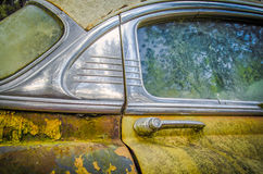 Door Handle and Window of 1953 Rusted Old Car. Door and window of a rusted yellow coupe car from the 1950s Stock Photos