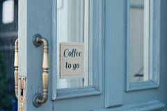 A door with a sign. Blue door with a small sign `Coffee to go stock photography