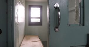 Opening prison door with sound. Door of solitary confinement cell opening to cell block hallway in old prison with sound stock footage