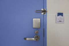 Door with stainless steel lock set and access control card. Blue door with stainless steel handle lock set and access control card in socket on wall royalty free stock photos