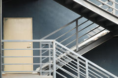 Door and stairs. Yellow door and metal stairs with gray wall Royalty Free Stock Photos