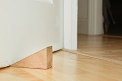 Door stopper. A wooden door stopper on a laminate floor royalty free stock image