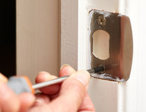 Door strike plate installation. Hands with screwdriver fixing a strike plate on the door Royalty Free Stock Images