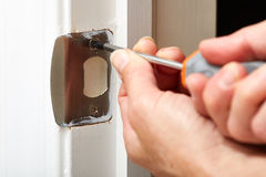 Door strike plate installation. Hands with screwdriver fixing a strike plate on the door Royalty Free Stock Image