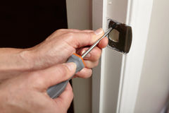 Door strike plate installation. Hands with screwdriver fixing a strike plate on the door Stock Photos