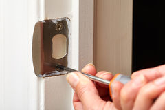 Door strike plate installation. Hands with screwdriver fixing a strike plate on the door Royalty Free Stock Photos