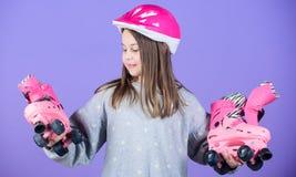 Door:sturen aan avonturen De slijtagehelm en rolschaatsen van de meisjes leuke tiener op violette achtergrond Actieve vrije tijd  stock afbeelding