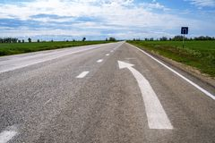 Door:sturen igns op de weg Wit die op zijn beurt het linkersymbool van de richtingspijl op de zwarte achtergrond van de asfaltweg stock afbeelding