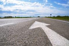 Door:sturen igns op de weg Wit die op zijn beurt het linkersymbool van de richtingspijl op de zwarte achtergrond van de asfaltweg stock foto