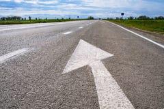 Door:sturen igns op de weg Wit die op zijn beurt het linkersymbool van de richtingspijl op de zwarte achtergrond van de asfaltweg royalty-vrije stock fotografie