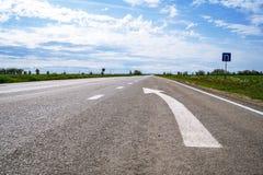 Door:sturen igns op de weg Wit die op zijn beurt het linkersymbool van de richtingspijl op de zwarte achtergrond van de asfaltweg royalty-vrije stock afbeelding