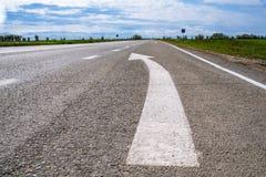 Door:sturen igns op de weg Wit die op zijn beurt het linkersymbool van de richtingspijl op de zwarte achtergrond van de asfaltweg stock fotografie