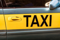 Door of a taxi car. With word TAXI written in black letters on a yellow stripe Stock Photography