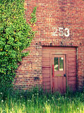 Door to Abandoned Station. Overgrown doorway to an abandoned brick train station Royalty Free Stock Image