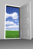 Door to bright new world. Open door with sky and green field in the background Stock Photo