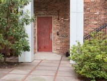 Red door under white arch. Door to building with white arch and bushes on each side Stock Images