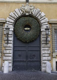 Door to Christmas. Monumental antique entrance door with Christmas decoration Stock Image