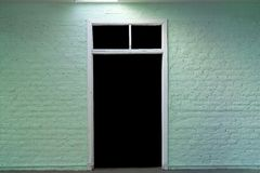 Door to darkness. Brick wall and door painted green and white stock photos