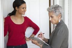 Door-to-door Solicitation. Black women greeting a solicitor at her front door royalty free stock photos