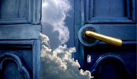Door to heaven. Open old blue door to heaven with brass handle. The sky and clouds invite You to a dream. Behind doors You find the power and happiness Stock Photos